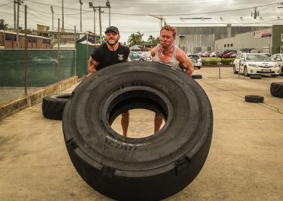 Two men flipping a large tire. Crossfit training.